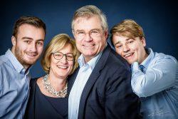 Familieportret: vader, moeder en twee studerende zoons