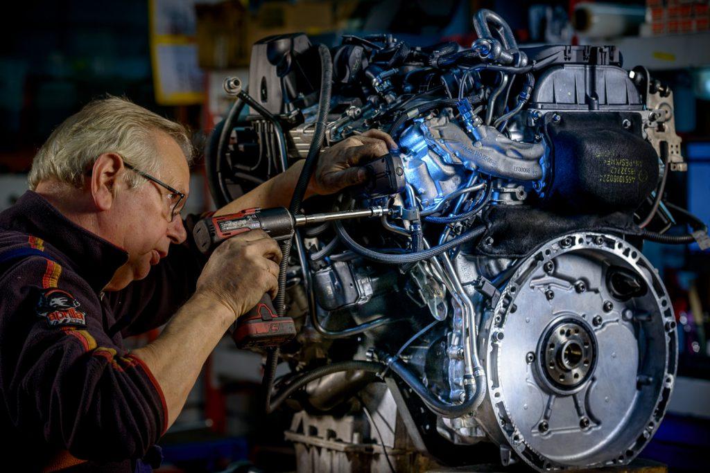 Industriële fotografie: monteur onderzoekt motorblok
