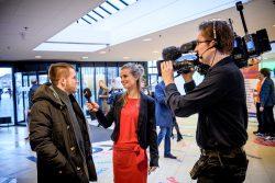 Een stralende interviewer en charmante cameraman vragen bezoekers naar jun verwachtingen.