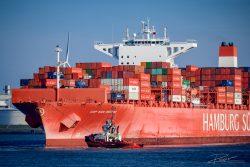 Containerschip wordt de haven in getrokken door een sleepboot. Foto gemaakt door industrieel fotograaf Rogier Bos in the port of Rotterdam