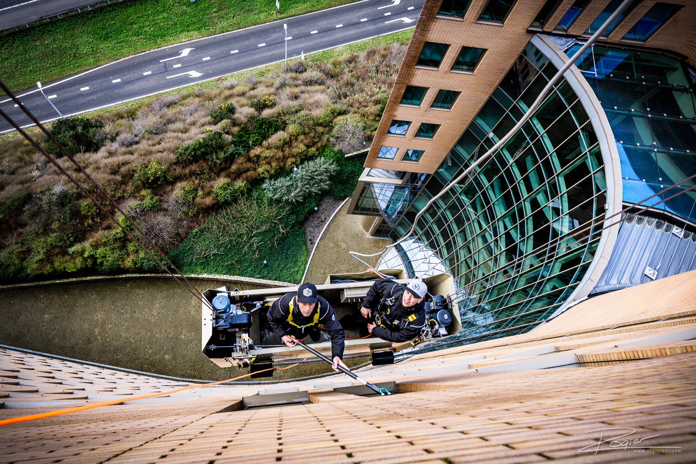 Even niet naar beneden kijken. Ik lig hier op de 15de verdieping, plat op mijn buik bovenop het gebouw, langs de A16 aan de oostkant van Rotterdam.