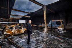 Ondernemer kijkt om zich heen in uitgebrand bedrijfspand