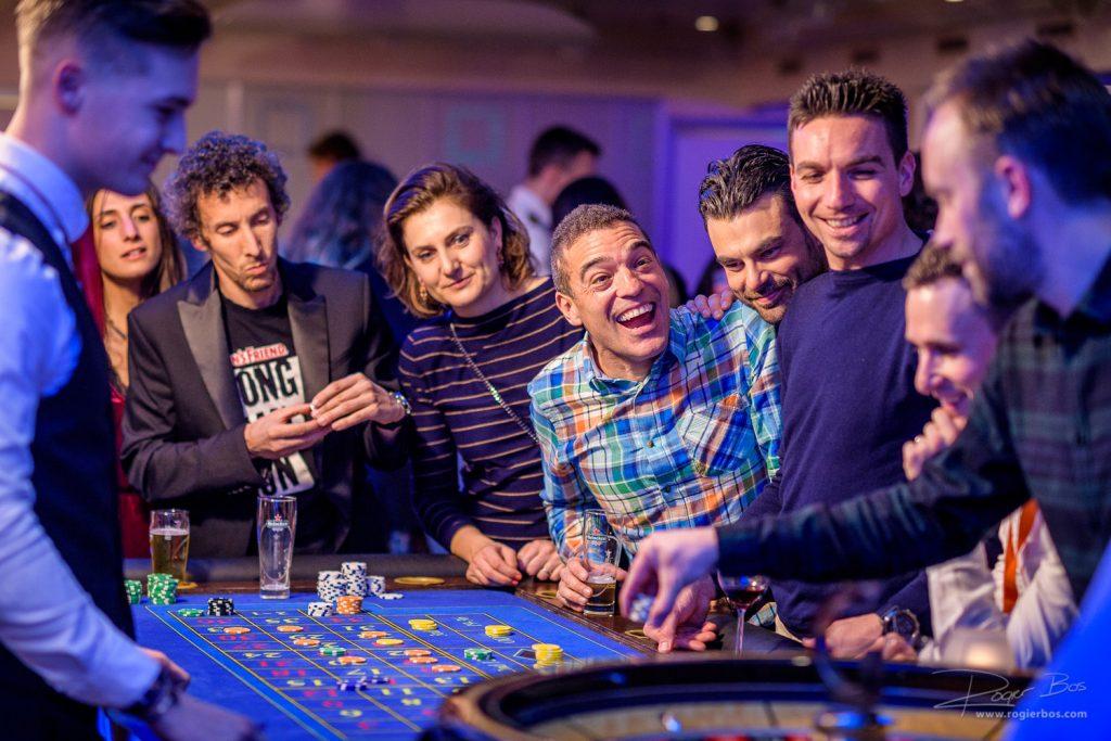 Collega's hebben plezier met elkaar aan de roulette tafel.