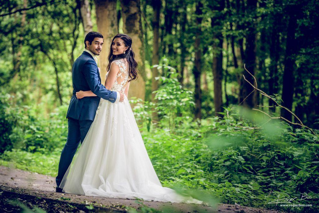 Trouwfoto van een mooi bruidspaar tussen de bomen van het Lage Bergse Bos