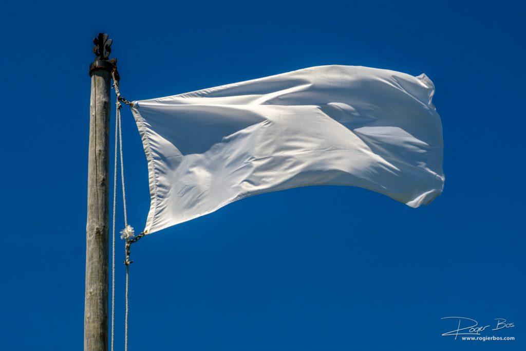 Foto van een witte vlag tegen een blauwe lucht