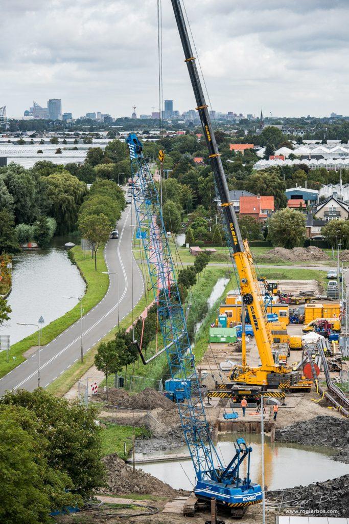 Overzichtsfoto van het plaatsen van een zinker met grote hijskraan. In de verte ligt Den Haag.