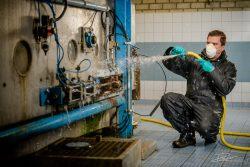 Schoonmaker aan het werk in rioolreinigingsinstallatie
