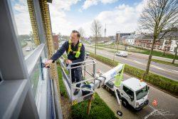 Schoonmaker maakt de ramen schoon met een hoogwerker in Roermond, Noord-Limburg