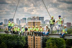 Groepsfoto van medewerkers in de bouw op Evenaar met Zuidas op achtergrond