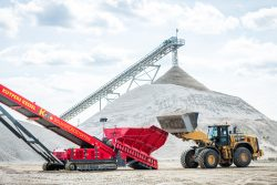 Industriële fotografie - laadschop brengt zand naar grote transportband