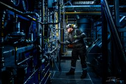 Industrial photography - operator checks valves in a technical installation