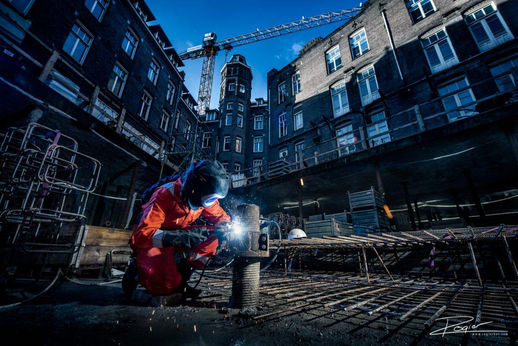 Lasser geconcentreerd bezig op een bouwproject in het centrum van Amsterdam. Foto door industrieel fotograaf Rogier Bos