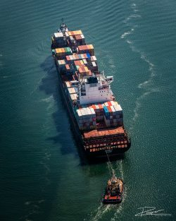 Containership Spyros V pulled into the Port of Rotterdam by two