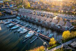 Drone foto woonwijk en jachthaven bij ondergaande zon